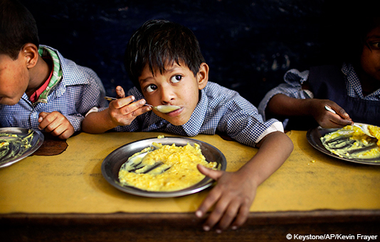 An Indian boy from a slum in Dehli eats lunch provided free by his school.