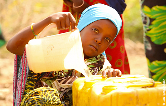 A girl in Ethiopia fills her canister with water.