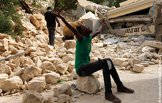 Cette femme, assise sur les décombres, a tout perdu suite au séisme en Haïti.