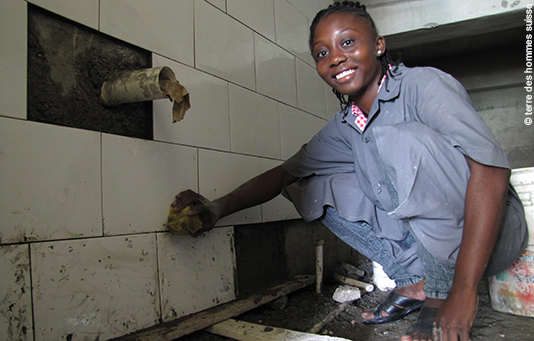 A young woman learning to lay tiles, trained by our partner relief organization Terre des Hommes Suisse.