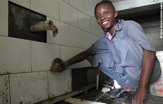 une jeune fille apprend à poser des carreaux grâce à la formation dispensée par notre ONG partenaire Terre des Hommes Suisse.