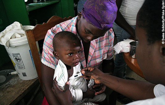 A doctor examines a young boy following the earthquake in Haiti.