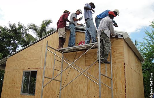 des ouvriers sur le chantier d'une maison démolie après le tremblement de terre en Haïti.