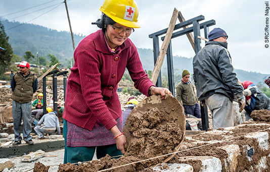A Nepalese woman trained in earthquake-proof construction helps to build new houses.