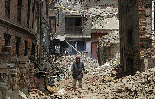 A man walks through the ruins of a town destroyed by the quake.