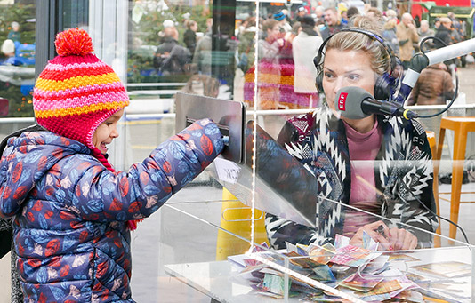 A child drops a donation into the 'Jeder Rappen zählt' collection box in Lucerne