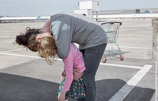 Une femme en situation de pauvreté porte son enfant dans les bras. Derrière elle, un chariot de supermarché vide.