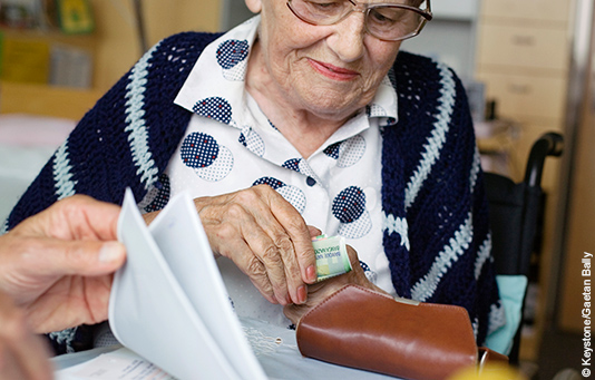 An elderly women counts the banknotes in her purse.