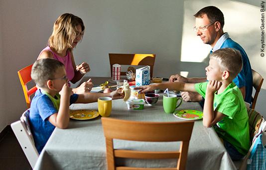 Des parents et leurs deux fils dans la précarité prennent le petit-déjeuner.