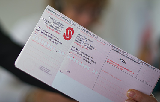 A volunteer holds up a payment slip for the camera on a national fundraising day