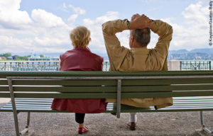 Donate with a bequest: An elderly couple sit on a park bench looking out at a lake.