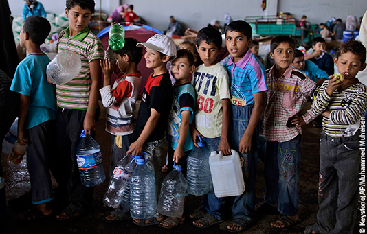 Syrian refugee children waiting in line to fill bottles with water