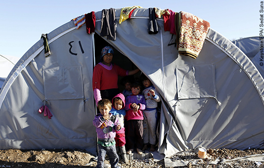 A Syrian family in front of their tent in a refugee camp.