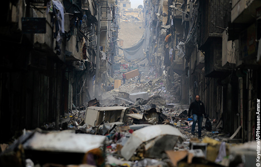 A man walks through the ruins of a street in Eastern Aleppo, Syria