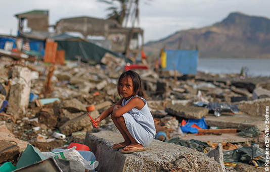 A Philippine girl sits in the ruins of her home in the city of Tacloban, destroyed by Typhoon Haiyan.