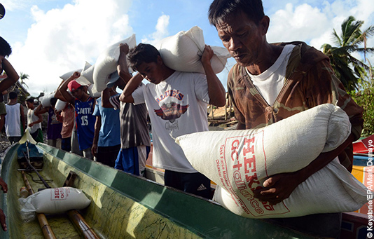 Victims of Typhoon Haiyan receive sacks of rice from our partner relief organization HEKS.