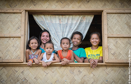 A Philippine family look out of the window of their newly built home.