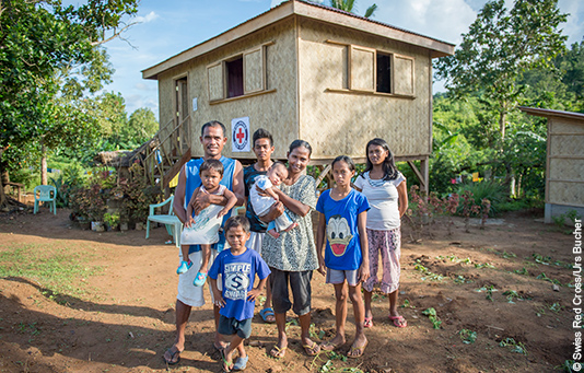A Philippine family in front of their reconstructed home.