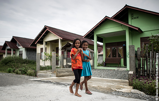 Two girls in Indonesia in front of a row of houses newly built for victims of the tsunami.