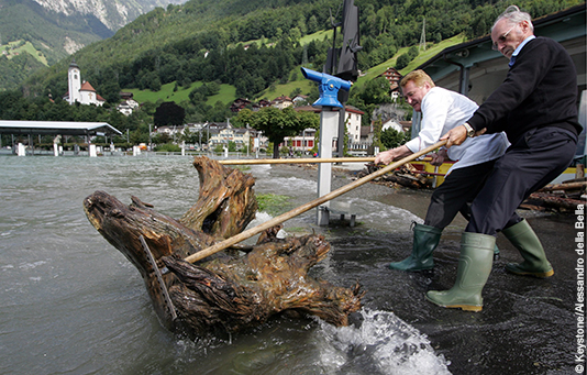 Two men fishing driftwood out of floodwater.