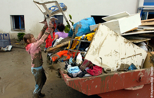 A girl throws storm-damaged furniture into a skip.