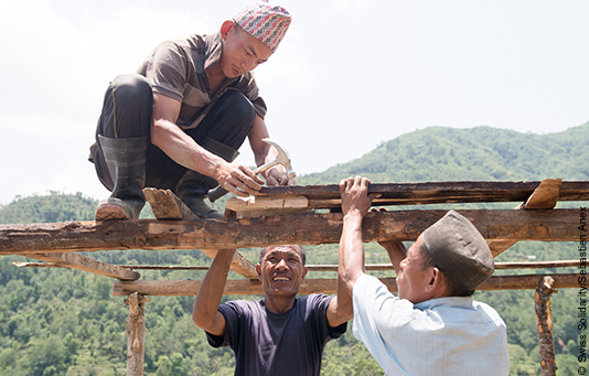 Nepalese men helping to reconstruct their homes.