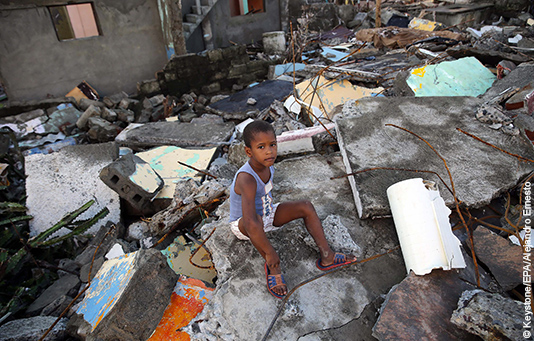 A child sits in the ruins of houses destroyed by Hurricane Matthew.