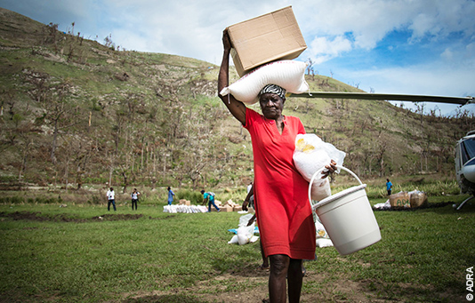 A woman on Haiti carries aid items she has received from our partner relief organization ADRA.