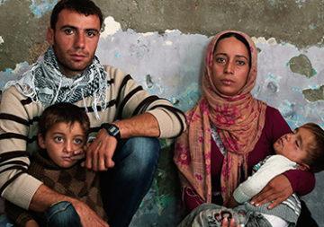 Un couple de réfugiés avec ses deux petits garçons dans une chambre à la frontière syrio-turque.