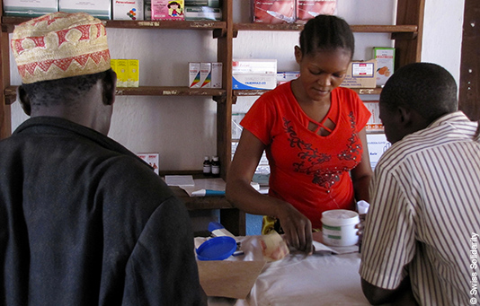 A sales assistant in a pharmacy explains how to administer anti-malarial medication.