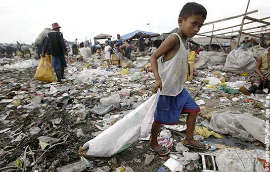 Un bambino filippino su una montagna di rifiuti in una baraccopoli.