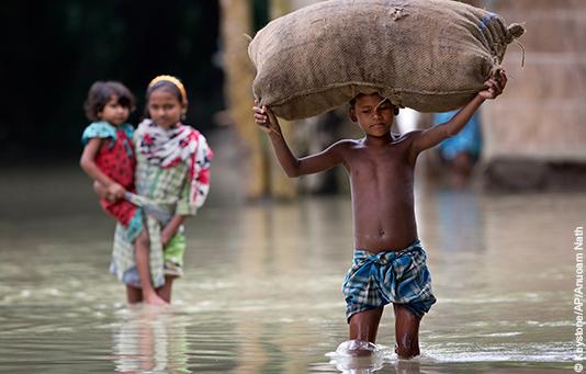 Un bambino indiano attraversa il suo villaggio inondato dal monsone portando un sacco sulla testa.