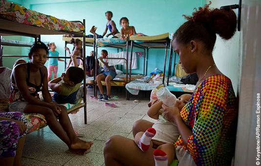 Familien suchen während einem Wirbelsturm Schutz in einer Notunterkunft.