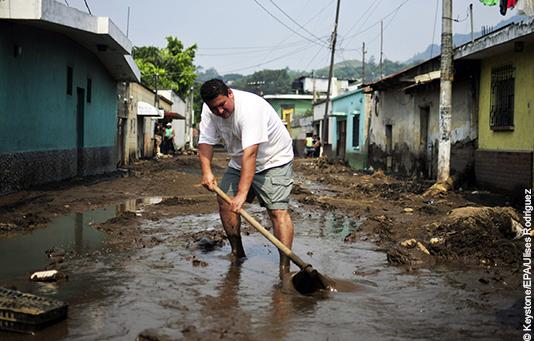 Ein Mann entfernt nach einem tropischen Wirbelsturm in Guatemala den Schlamm von einer Strasse.
