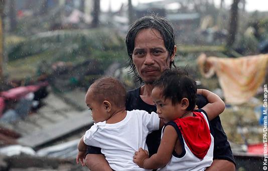 Ein Mann, dessen Haus vom Taifun Haiyan zerstört wurde, hält seine beiden Söhne im Arm.