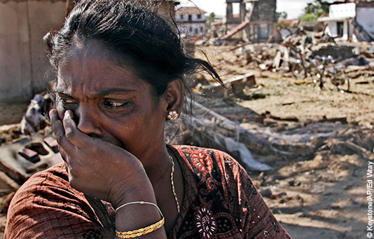 Eine Frau in Sri Lanka vor ihrem vom Tsunami zerstörten Haus.