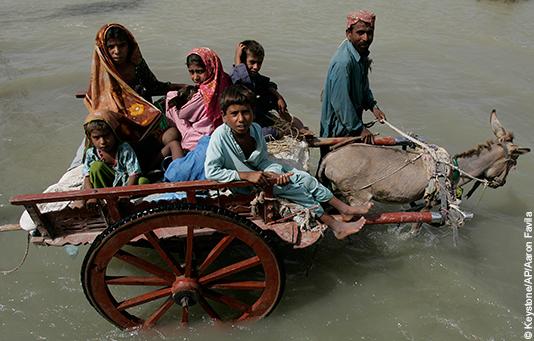 Eine pakistanische Familie durchquert die überfluteten Strassen auf einem Wagen, der von einem Esel gezogen wird.