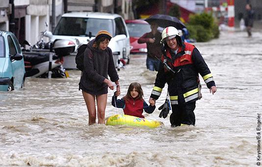 Ein Feuerwehrmann und eine Frau ziehen ein Mädchen in einem Schlauchboot durch die überschwemmten Strassen von Bern.